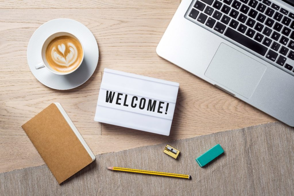 Welcome sign lying on desk with coffee, laptop, and notebook